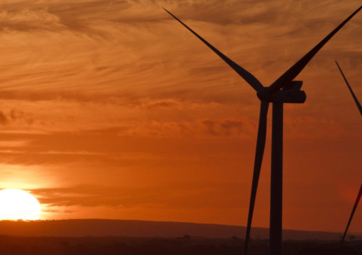 Two Vestas wind turbines overlooking a bright red and orange sky at sunset/sunrise