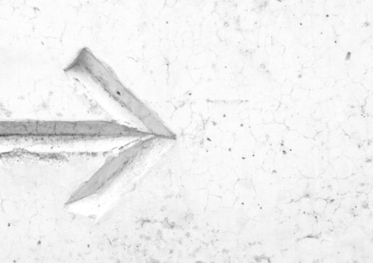 Carved arrow in a concrete wall showing directions