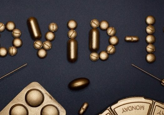 Banner image showing Covid-19 in gold pills and syringe