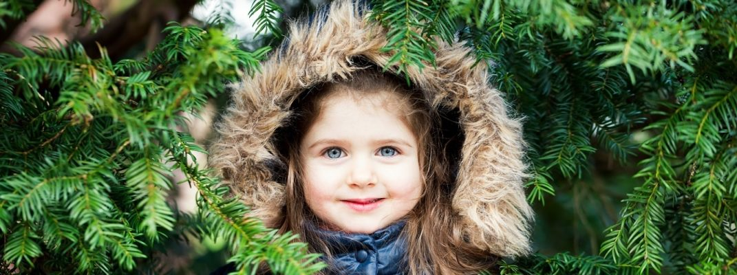 Little girl peeking through the branches of a Christmas tree